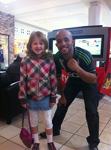 UFC fighter Mighty Mouse posing with a fan