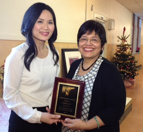 Estela Ortega, right, executive director of El Centro de La Raza in Seattle, presented the Corporate Citizen of the Year Award to Comcast in Seattle. Receiving the award was Diem Ly, left, manager of external affairs for Comcast in Washington.