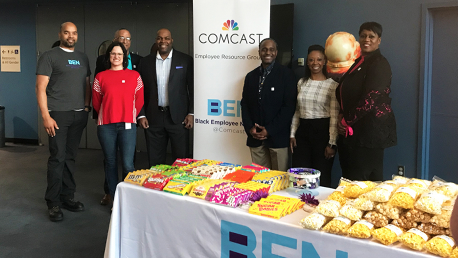 The Comcast Employee Resource Group and the Comcast Black Employee Network standing in-front of a Comcast branded banner.