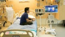 A young child in a hospital setting playing video games.