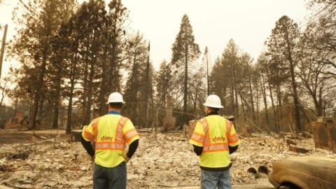 Two Xfinity technicians examine fire damage in a neighborhood